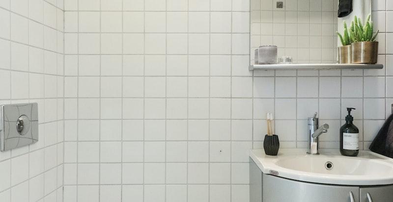 Mosaikkfliser på gulvet gjør badet moderne og pent.