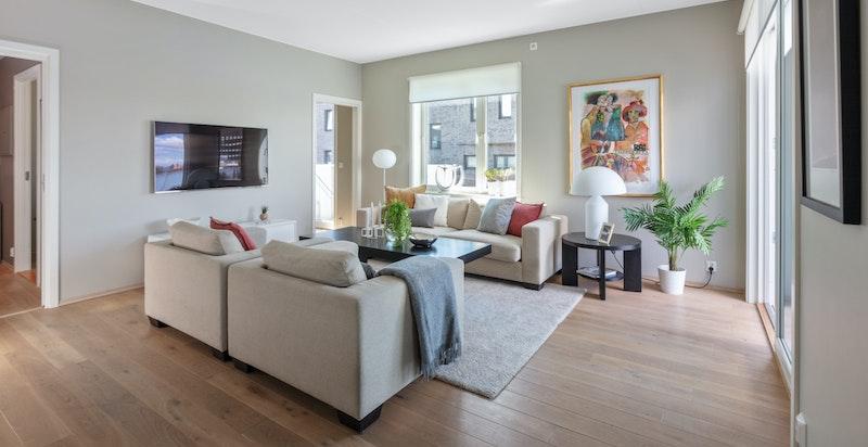 Leiligheten har en romslig stue med god plass til sofa og TV-løsninger.