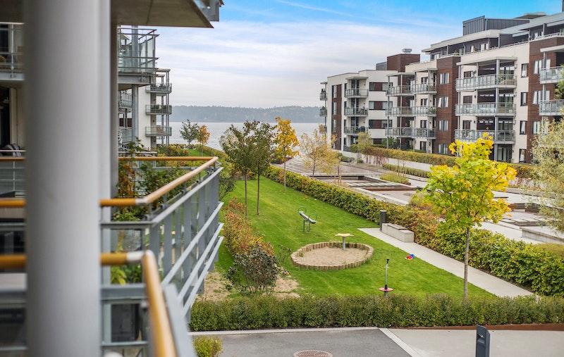 Flott utsyn fra balkongen mot fellesområder og ned til sjøen