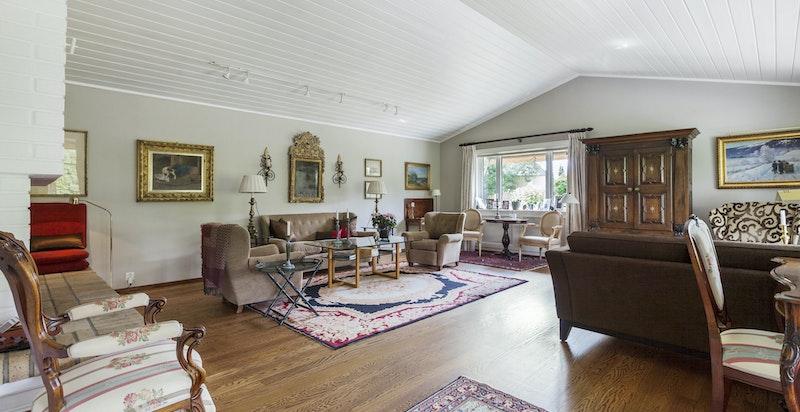 Lys og åpen stue med god takhøyde og store vindusflater