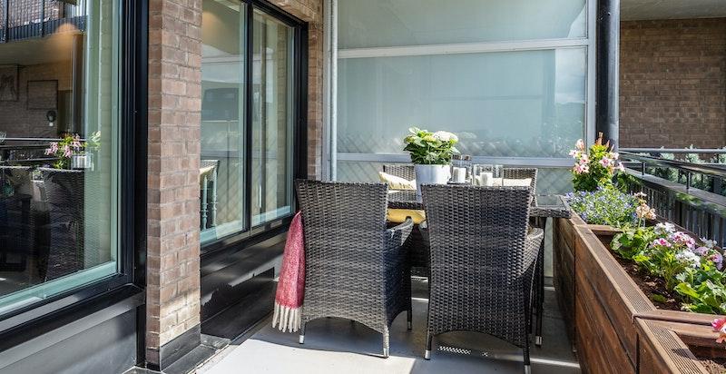 Lun overbygget syd/vest-vendt balkong med meget gode solforhold