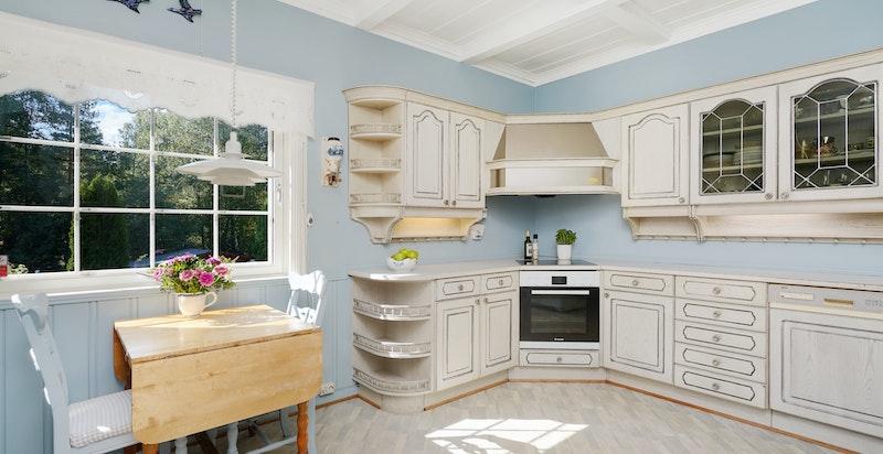 Stort kjøkken med innredning fra Sivesind, integrerte hvitevarer og frokostplass ved vinduet