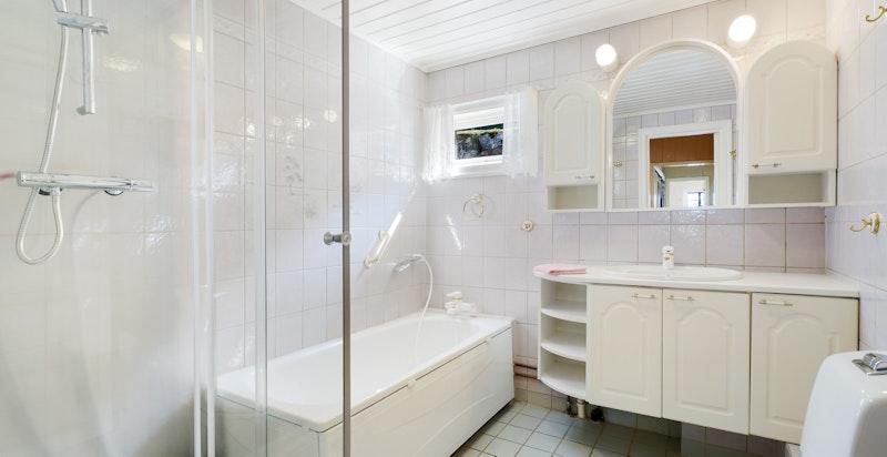 Flislagt bad med wc, servant, skapplass, dusj og badekar.