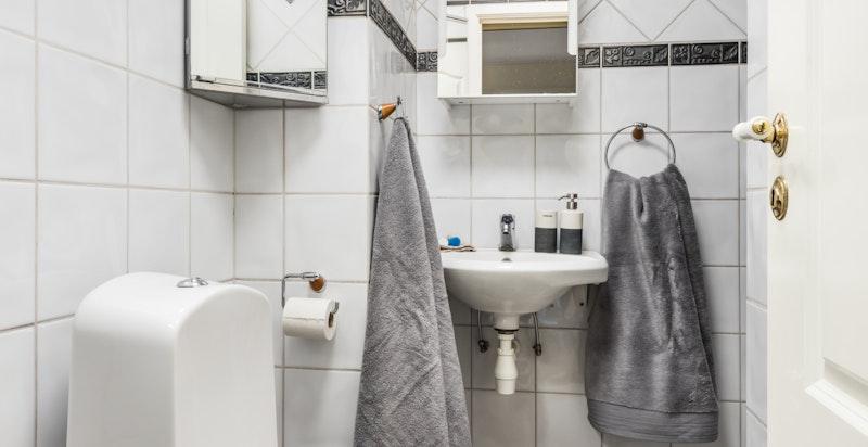 Flislagt dusjbad med toalett.