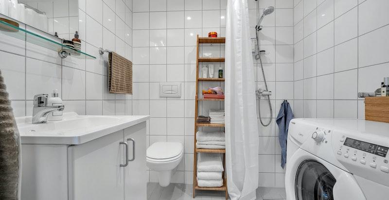 Lyst og moderne baderom med dusjhjørne, vegghengt klosett, opplegg for vaskemaskin og servant med skap og speil