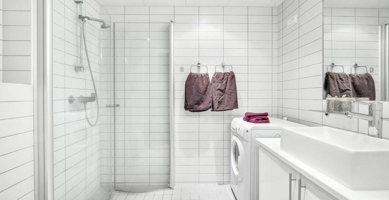 Lyst og tidsriktig bad med dusjhjørne og opplegg for vaskemaskin