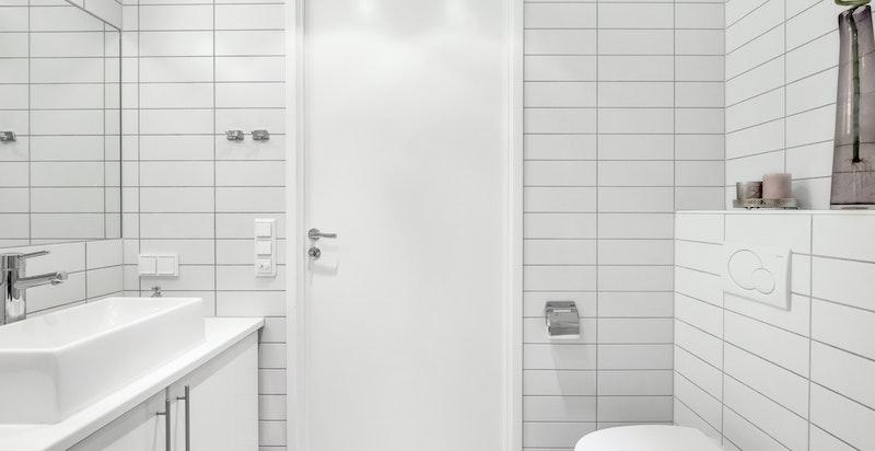Badet har også vegghengt kloset, og servant med underskap og speil