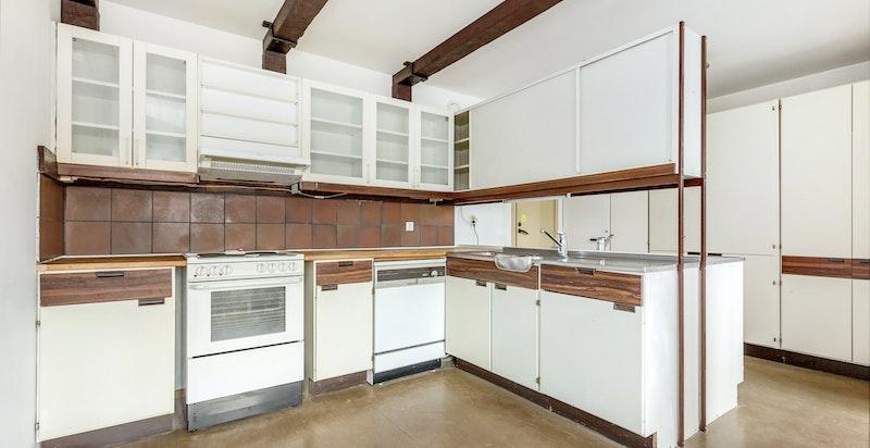 Original kjøkkeninnredning med laminat front, heltre benkeplate, rustfri oppvaskbenk, opplegg for oppvaskmaskin, ventilator og fliser over benk.