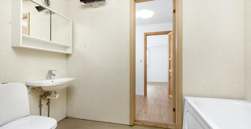 Bad 1 er utstyrt med badekar, toalett og servant.