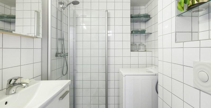 Pent og praktisk baderom med vaskemaskin, dusjhjørne meddører i glass og servant med underskap.