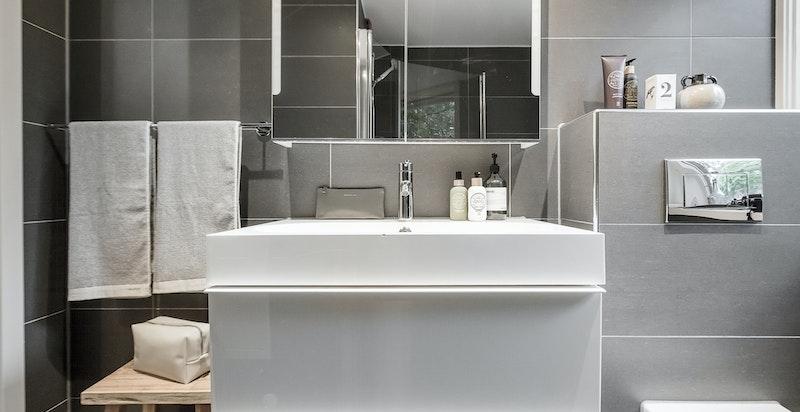 Badet inneholder servant, vegghengt wc og dusjhjørne, samt opplegg til vaskemaskin/tørketrommel.