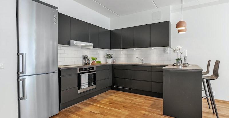 Kjøkkeninnredning med glatte fronter, integrerte håndtak, to stålkummer med blandebatteri, laminat benkeplater, plass til frittstående kjøl/frys, integrert komfyr med induksjonstopp, ventilator/avtrekksvifte, integrert oppvaskmaskin
