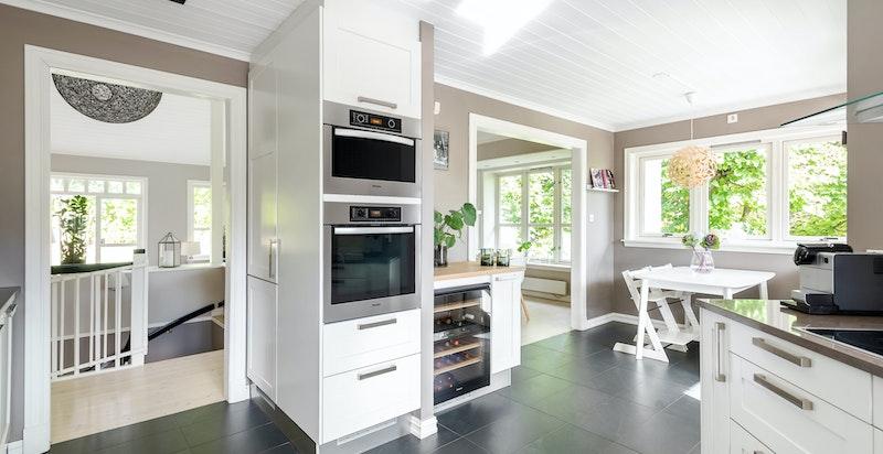 Lunt og funksjonelt kjøkken med varmekabler med integrerte hvitevarer og vinskap fra Miele.