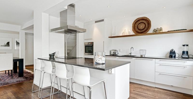 Kjøkkenet har en stor kjøkkenøy med en praktisk barløsning