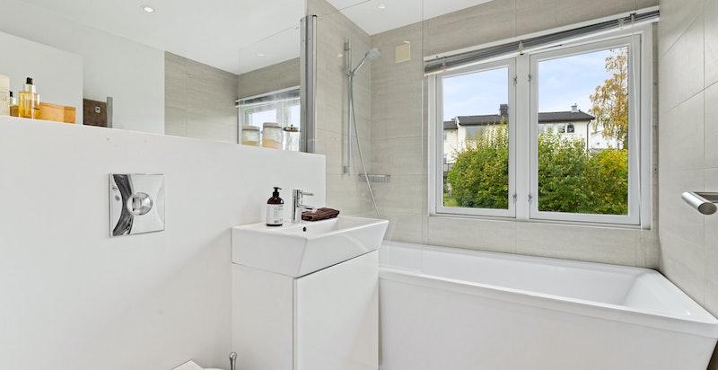 Bad/wc i 2. etasje innredet med servantinnredning, vegghengt toalett og badekar med dusjvegg.