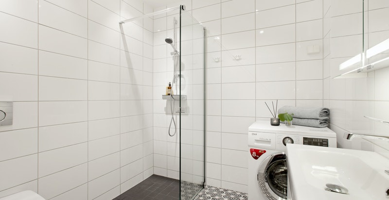 Badet er innbydende og består av dusjhjørne med bl.batteri og glass/skyvedør på en side, vegghengt toalett, innredning med heldekkende servant med ett-greps bl.batteri og overskap med speil og lys.