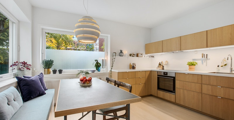 Kjøkkenet er sosialt og særdeles gjennomført med stor spiseplass med benk, store vinduer i hjørnet og tidsriktig innredning.