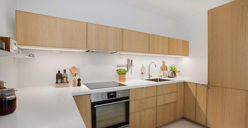 Kjøkkenet har godt med benkplass og alle hvitevarer er integrert.