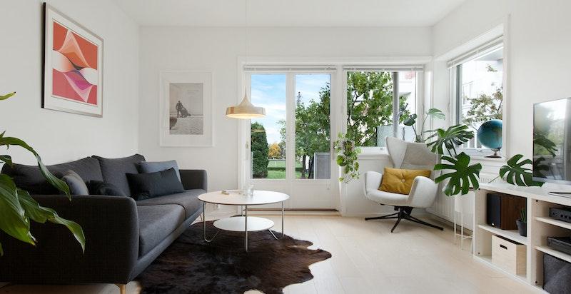 Stuen er lys og pen med flott utsyn til hyggelig felles hage.