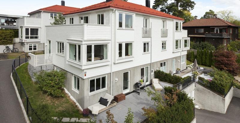 Fasade - Halvpart av vertikaldelt tomannsbolig, hvorav denne boligen vender mot syd