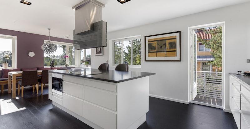Kjøkkenet er tilknyttet spisestue og har utgang til terrasseplatting og hage