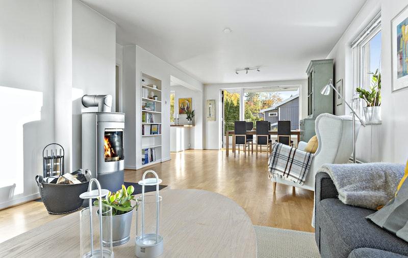 Stor og lys stue/spisestue med god vindusflate og utgang til terrasse og hage