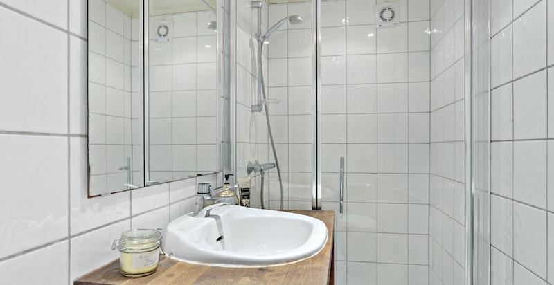 Badet ble oppgradert i 2006 med fliser og varmekabler på gulv, dushjørne med glassvegg samt servant med benk og hylle under.