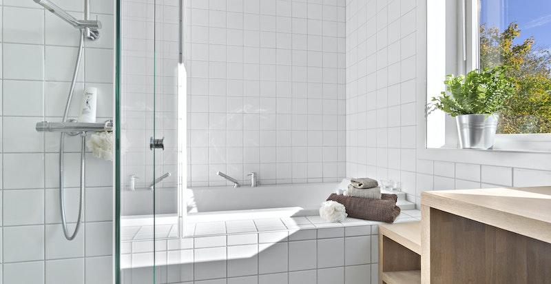 Deilig med innfliset badekar delvis plassert i egen nisje. I tillegg god benkplass til lagring av håndklær og toalettartikler