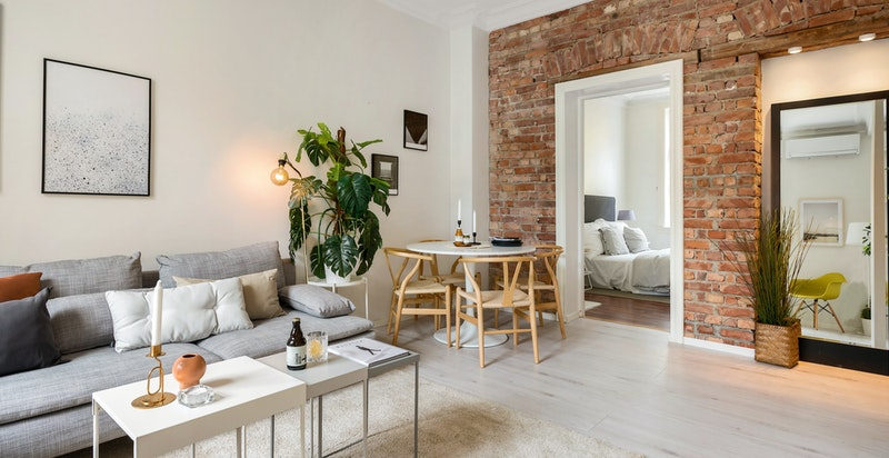 Den flotte teglsteinsveggen i stuen gir boligen det klassiske, originale preget.