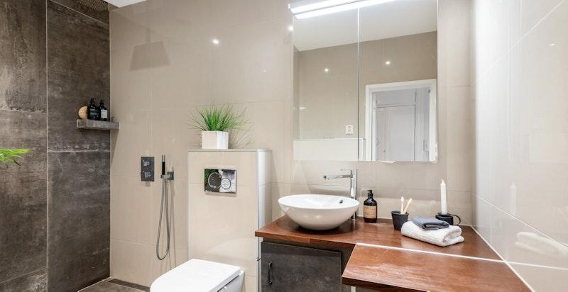 Nyere, pent og tidsriktig badeværelse med regnfallsdusj, toalett og servant.