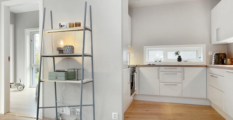 """Kjøkkenet er praktisk designet i """"hestesko-form"""" delvis adskilt fra stuen."""