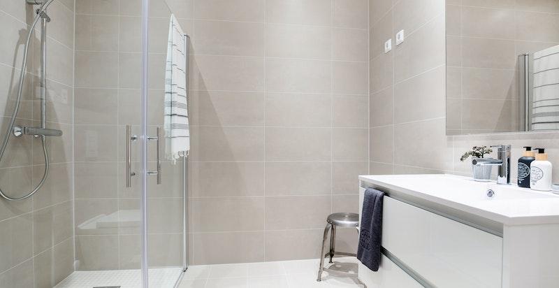 Leiligheten har et delikat bad med italienske fliser type 30x60 på vegg, 30x30 på gulv og mosaikkfliser på gulv i dusjsonen. Elektriske varmekabler i gulv og downlightsbelysning i himling.