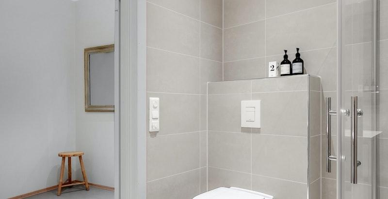 Badet er utstyrt med hvit baderomsinnredning med heldekkende servanttopp, ettgreps armatur, speil over innredning, vegghengt toalett og dusjhjørne med innfellbare dusjvegger i glass. Det er opplegg for vaskemaskin og tørketrommel.