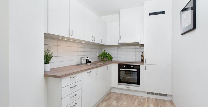 Kjøkkenet har integrert induksjonstopp, stekeovn, oppvaskmaskin, kjøleskap og fryseskap.