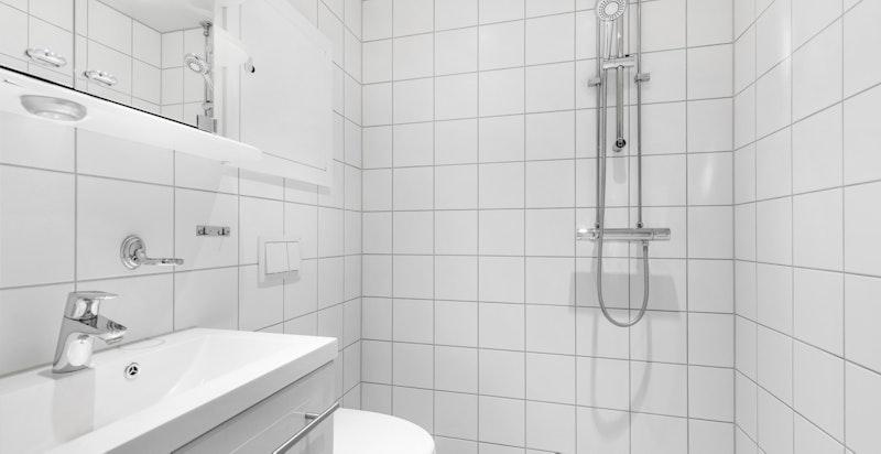 Badet utstyrt med baderomsinnredning med heldekkende servant over to skuffer med oppbevaringsplass, ett greps blandebatteri og speilskap med ekstra belysning.
