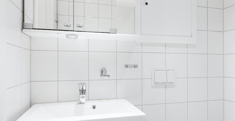 Det er veggmontert toalett samt veggmontert dusj. Nye vann- og avløpsledninger (rør-i-rør). Vannskap er plasser på badet.