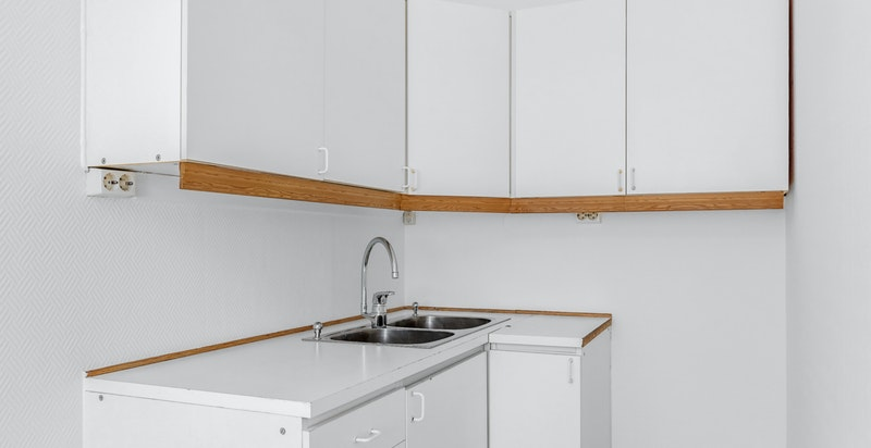 Delvis adskilt kjøkken med eldre kjøkkeninnredning. Kjøkkeninnredning består av hvite laminat fronter, hvit laminat benkeplate og rustfri oppvaskkum med ett greps blandebatteri.