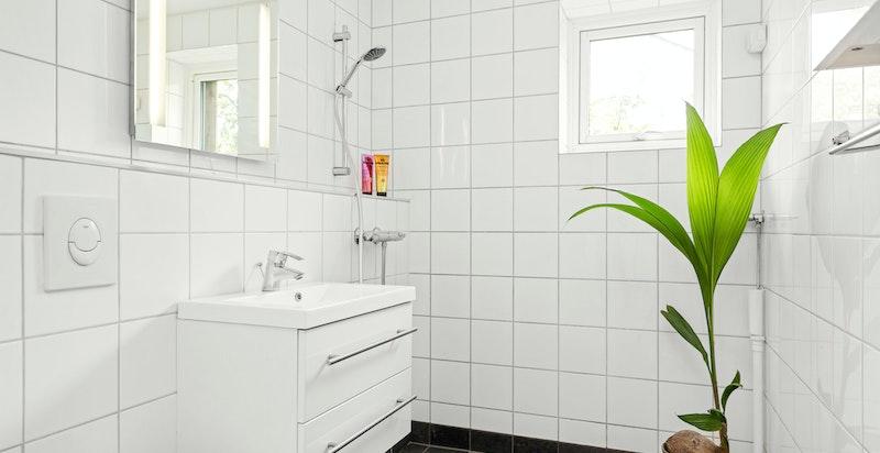 Flislagt bad i 2. etasje som inneholder wc, servant og dusjhjørne.
