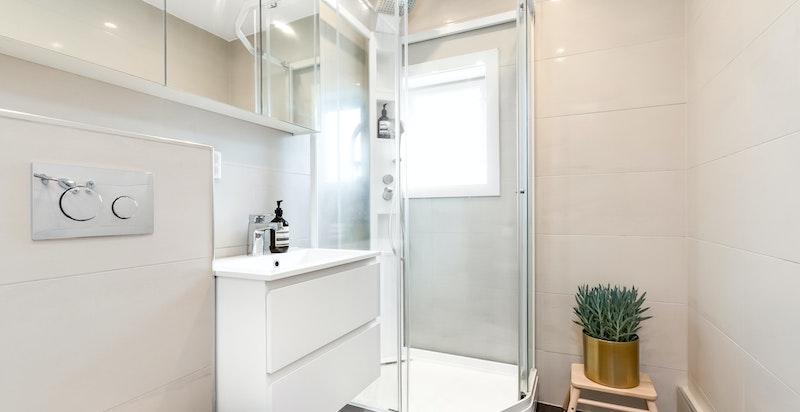 Et lekkert og godt utnyttet dusjbad/toalett.