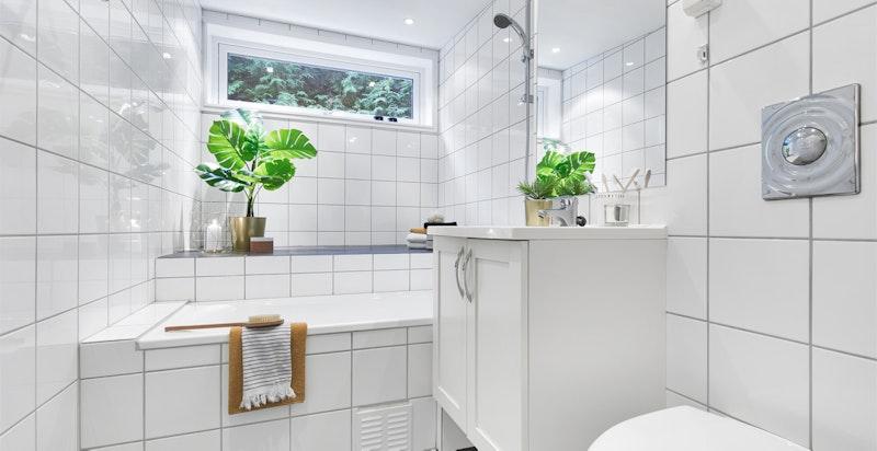 Flislagt baderom med badekar. Opplegg for vaskemaskin.