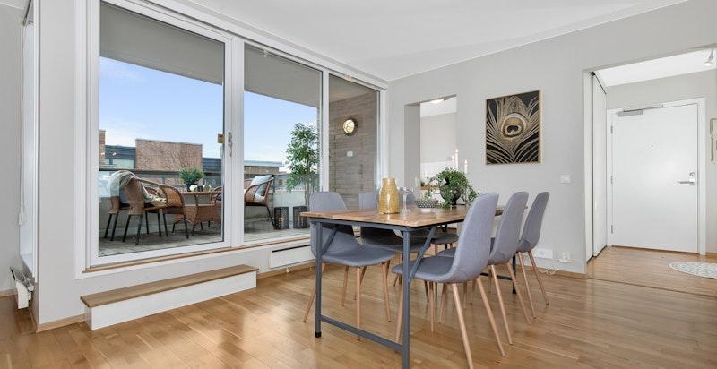 Åpen stue/spisestue med godt lysinnslipp gjennom store vindusflater.