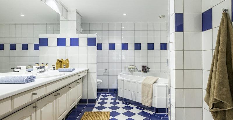 Stort bad i tilknytning til hovedsoverom med dusjnisje og badekar