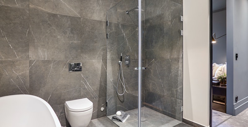 Badet i tilknytting hovedsoverom inneholder dusjhjørne, badekar, servant og vegghengt wc.
