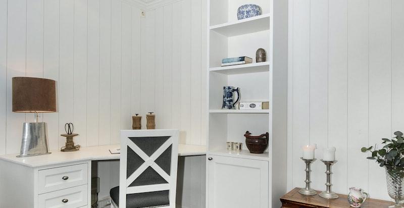 Arbeidshjørne/del av stue i praktikantdel  med plassbygd skrivebord og hyller