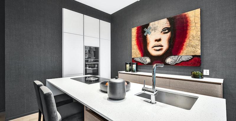 Hyggelig stue med åpen kjøkkenløsning. Tidsmessig kjøkkeninnredning fra HTH med integrert kaffemaskin, komfyr, oppvaskmaskin, kjøleskap og fryser