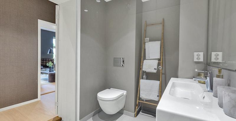 Svært delikat dusjbad/wc med varmekabler i gulv. Dusjløsning med skjermvegg i herdet glass. Vegghengt wc. Servant med underskap med speil og belysning