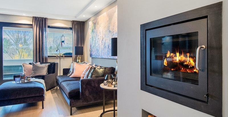Hyggelig og moderne peisovn innfelt i stueveggen med plass til ved under