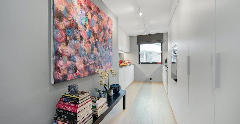 Kjøkkenet ligger tilbaketrukket fra stuen, men i en åpen løsing for enkel adkomst og naturlig tilknytning til spiseplass