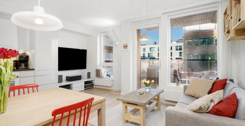 Stue og kjøkken i åpen løsning med store vindusflater