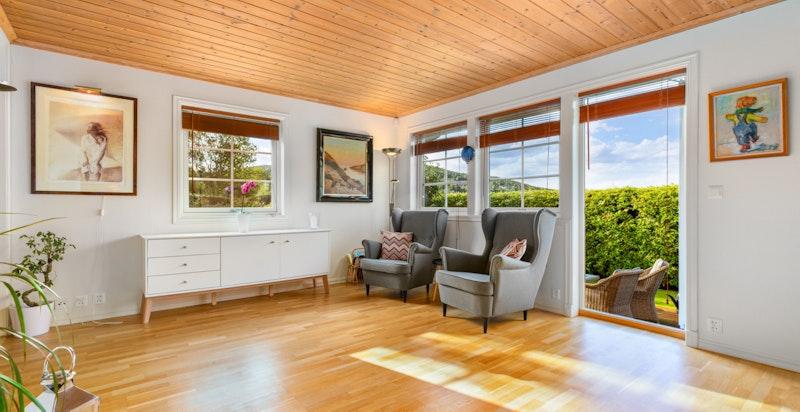 Lys, åpen stue med utgang til hage